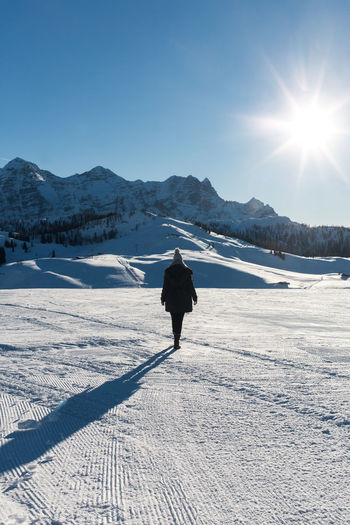 Rear View Of Woman Walking On Snowcapped Field During Winter