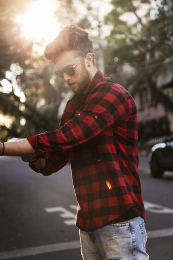 Man wearing plaid shirt and sunglasses while standing on road
