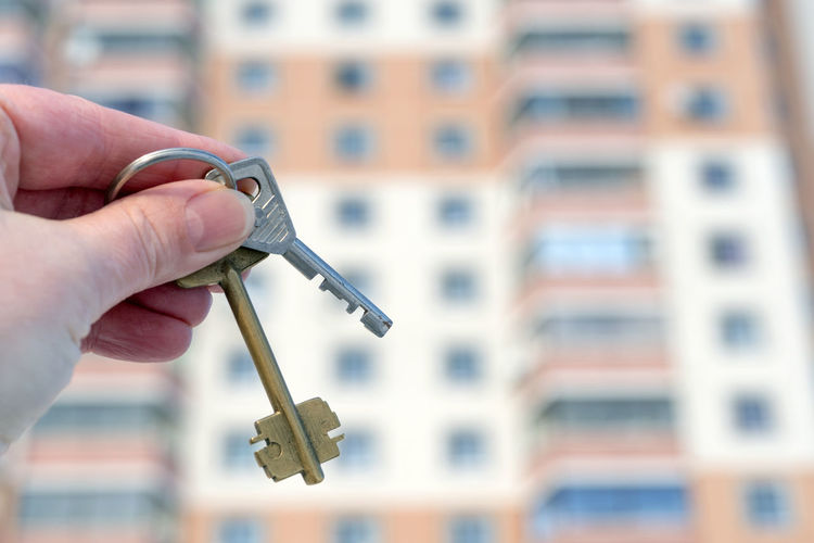 The hand of a white man holds the keys on the background of an apartment building Apartment Buildings Hand Tool Keys Photography