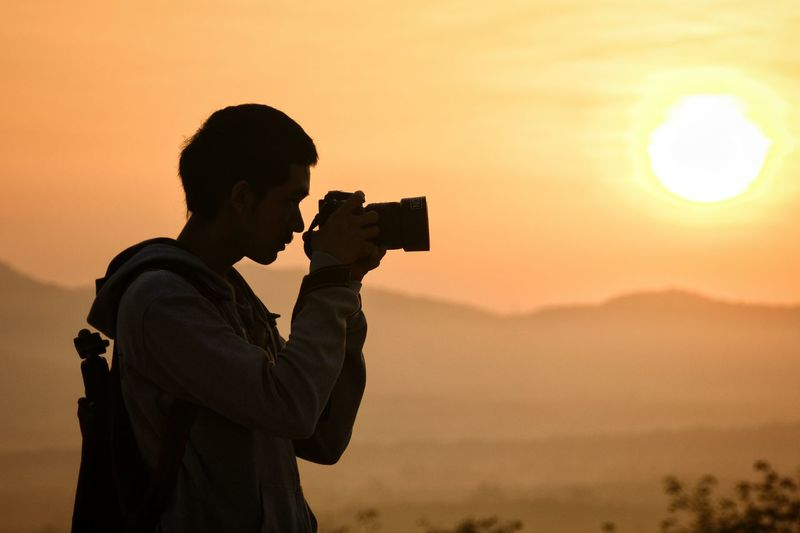 Side view of man photographing with camera against sky during sunset
