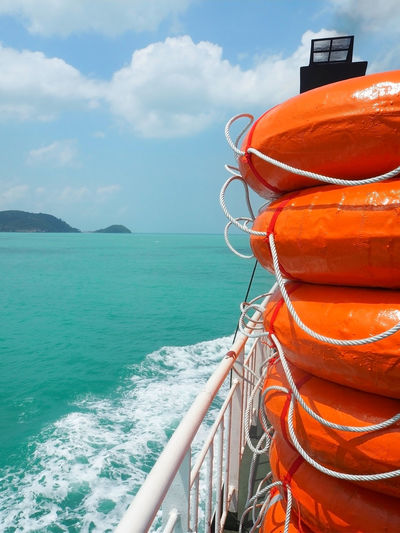 Stack of orange inflatable rings on boat deck in sea against sky