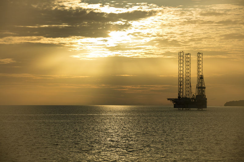 A jack-up rig standby at anchorage for maintenance during sunset Anchor Anchorage Life Beauty In Nature Business Finance And Industry Day Drilling Rig Golden Hour Horizon Over Water Industry Jack Up Rig Maintenance Nature Offshore Platform Outdoors Scenics Sea Sea And Sky Seascape Seascape Photography Sky Sun Rays Through The Clouds Sunset Sunset Silhouettes Water