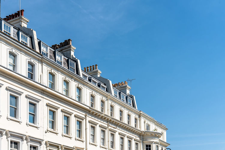 Luxury english victorian houses in notting hill in london against blue sky.