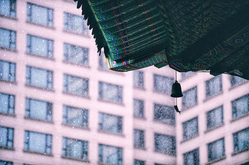 Low angle view of bell hanging on roof during snowfall