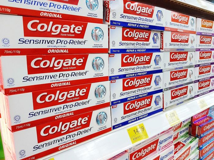 Colgate toothpaste brand on a retail shop shelf. No People Business Indoors  Full Frame Bathroom Colgate  Tooth Toothpaste Clean White Healthy People Teeth Healthcare And Medicine Care Medicine Sale Selling Buy Utility Business Market Retail  Price Tag Cleaning