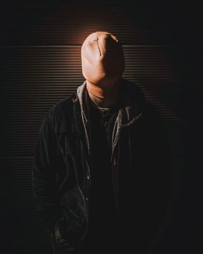 Man Face Covered Knit Hat While Standing Against Wall At Night