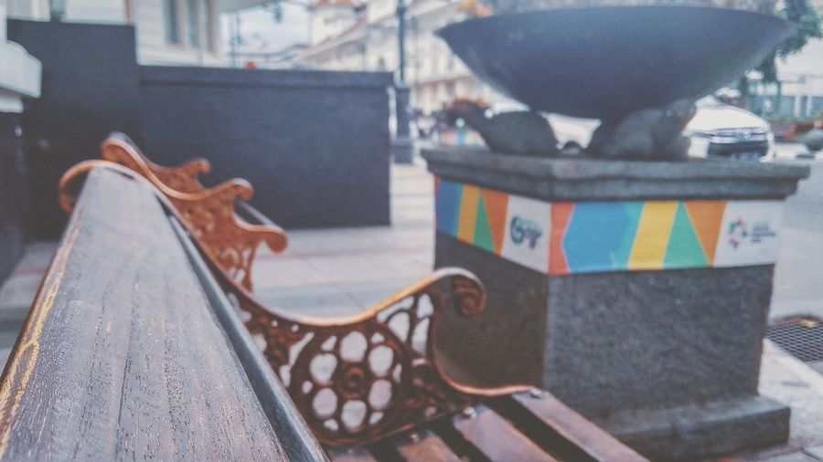Close-up of empty bench on table in city