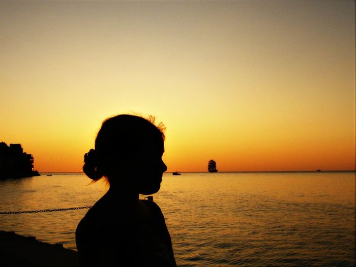 Side view of silhouette teenage girl standing at beach against sky during sunset