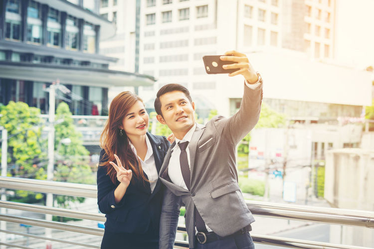 Portrait of young woman using smart phone in city
