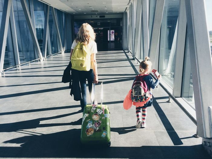 Rear view of mother pulling suitcase while walking with daughter at airport corridor