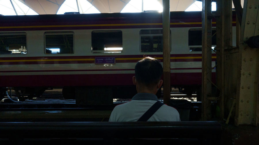Rear view of man on train at railroad station