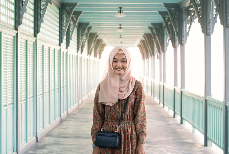 Portrait of smiling young woman wearing hijab standing on footbridge