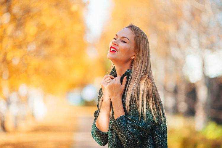 Beautiful young woman standing by autumn leaves