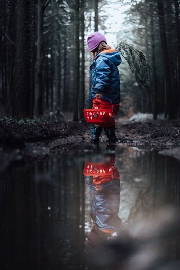 Reflection Of Girl Holding Basket In Puddle Standing Against Trees In Forest