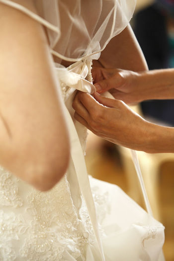 Close-up of woman adjusting wedding dress for bride