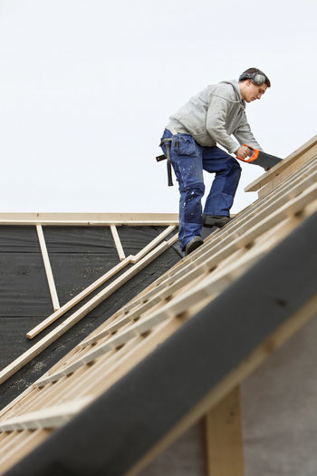 Low angle view of man working on roof against sky