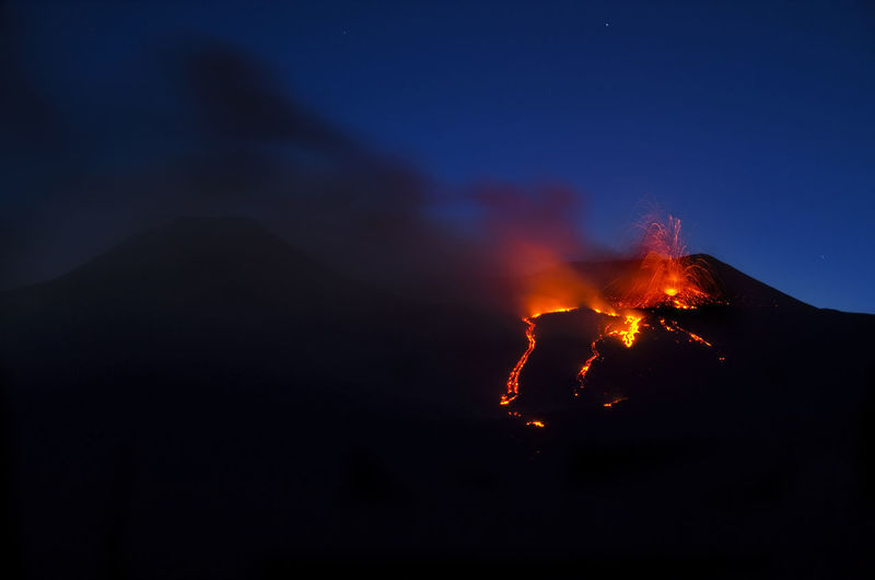 Silhouette mt etna against sky at night
