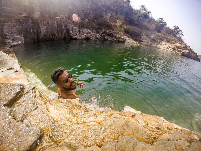 Portrait of young man wearing sunglasses swimming in sea