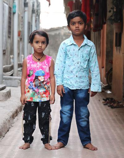 Full length portrait of happy siblings