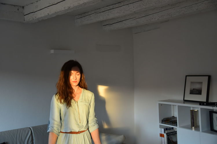 Portrait of woman standing against wall at home