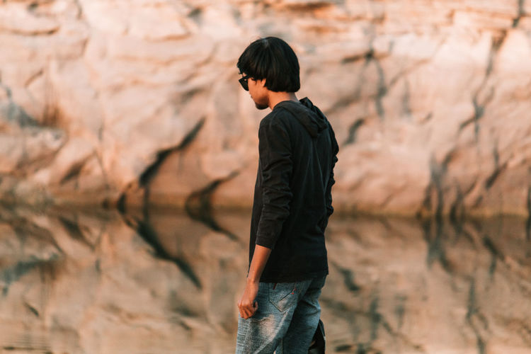 Man walking against rock formation
