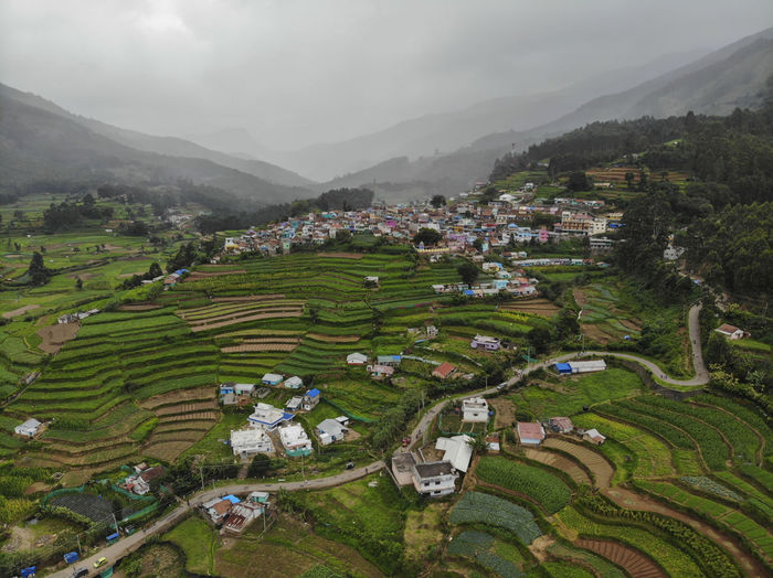Aerial View Of Agricultural Field And Houses Against Sky