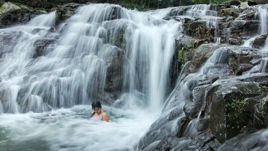 Woman Relaxing In Waterfall At Forest