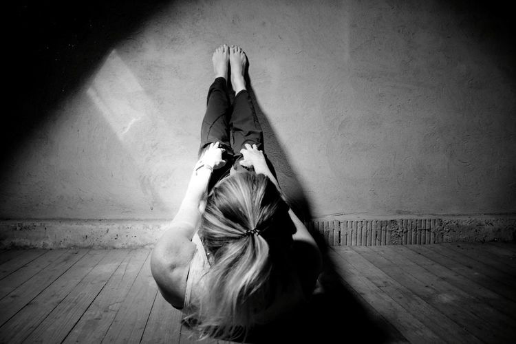 Woman dancing on floor against wall at home