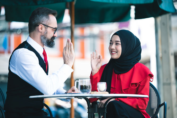 Smiling young couple sitting on table at cafe