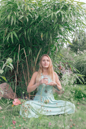 Portrait of young woman holding wineglass while sitting against plants