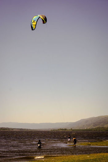 People paragliding on wet field against clear sky