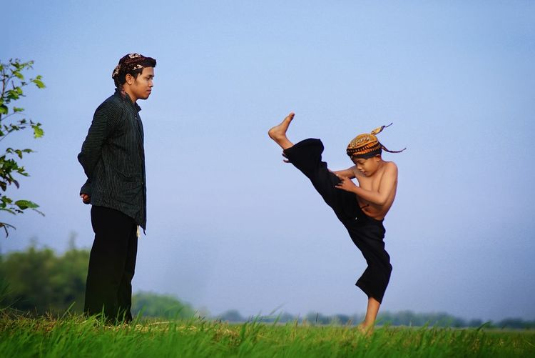 Male instructor watching at boy practicing kung fu on field against sky