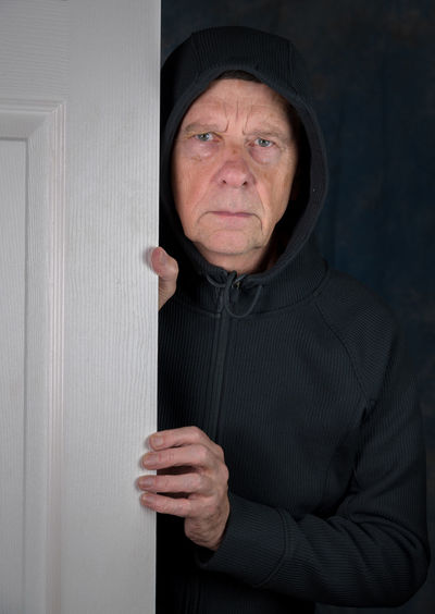 Portrait of man wearing hood while standing at door