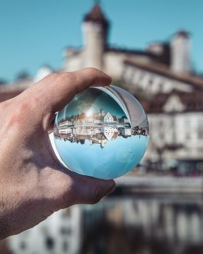 Cropped hand holding crystal ball with reflection of city