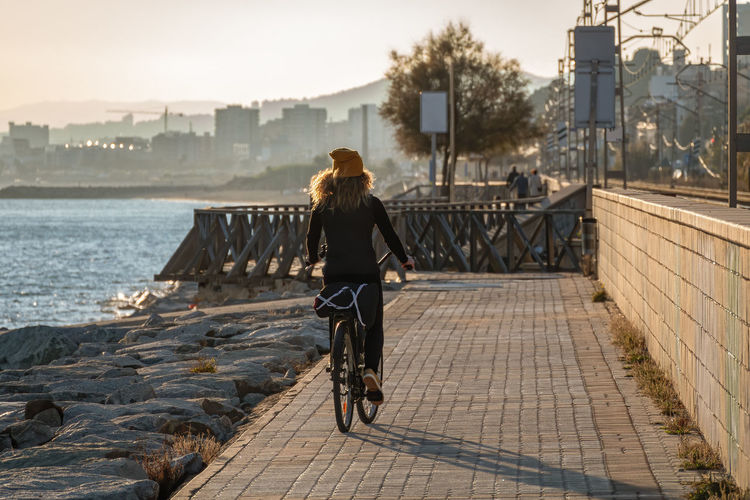 Rear view of woman riding bicycle on promenade in city