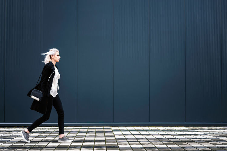 Side view of young woman walking on footpath against wall
