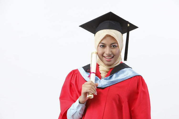 malay woman with red graduation gown Achievement Asian  Celebration Graduation Happy People Isolated Woman Beautiful Woman Cap Ceremony Certificate Cut Out Education Graduation Gown Holding Malay Ethnicity Mortarboard One Person Portrait Smile Studio Shot Success University Student White Background Young Adult
