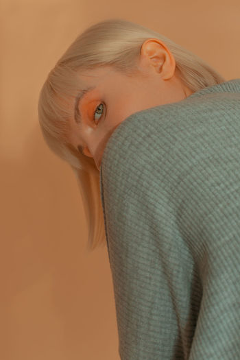 Gotcha The Week on EyeEm TheWeekOnEyeEM Beautiful Woman Beauty Beige Background Blond Hair Close-up Colored Background Contemplation Hairstyle Looking At Camera Orange Shadow Turtleneck The Fashion Photographer - 2018 EyeEm Awards The Portraitist - 2018 EyeEm Awards