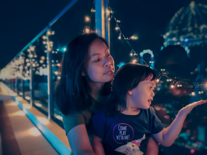 Young asian woman accompanied her daughter playing with christmas led lights. Family Time Fairy Lights Family Time Night Blur Background Bokeh Neon Style Cuddling Love Cute Blue Hour Child Togetherness Childhood Smiling Girls Females Happiness Young Women Single Mother Preschooler