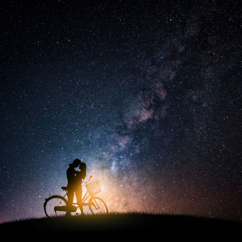 Silhouette Couple Romancing By Bicycle Against Star Field At Night