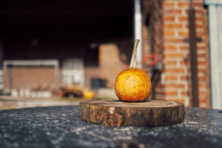 Close-up of orange on table against wall