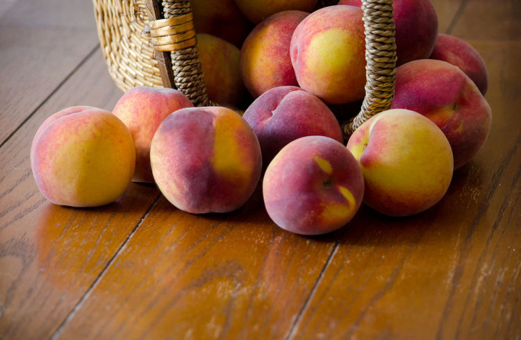 closeup of fresh picked peaches spilling out of a basket Agriculture Basketball Fall Colors Freshness Nature USA Basket Container Food Food And Drink Freshness Fruit Healthy Eating Indoors  Juicy Fruit Michigan Peaches Orange Color Organic Peanuts Peach Spilling Out Still Life Table Wellbeing Wood - Material Yellow