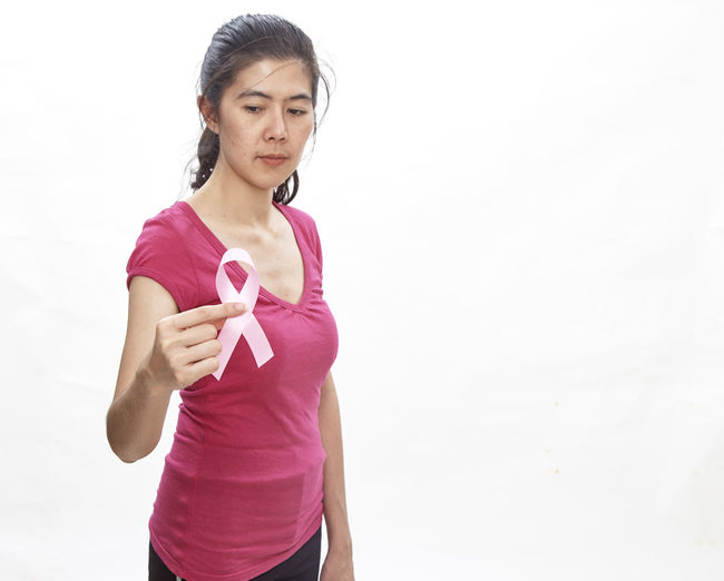 Woman holding breast cancer awareness ribbon against white background
