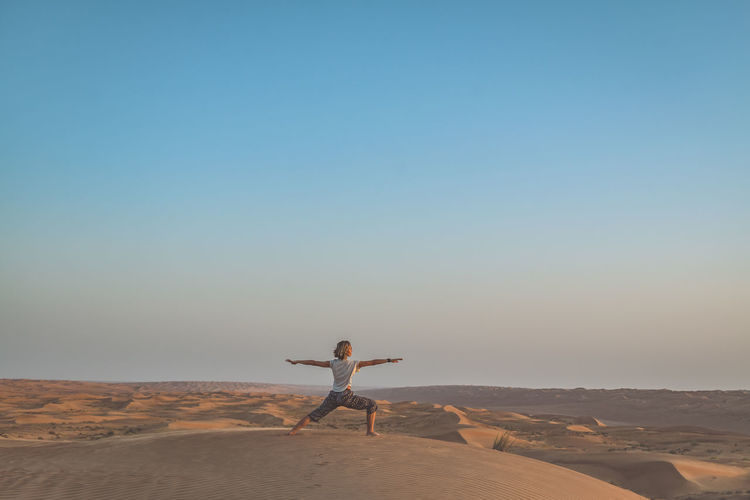Woman Practicing Yoga In Desert