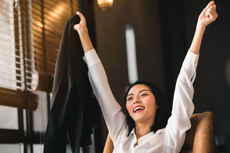Cheerful businesswoman with arms raised at office