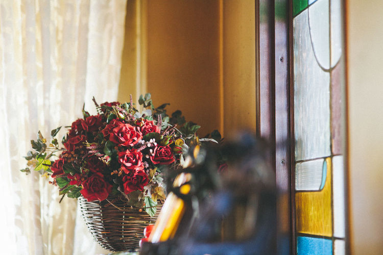 Close-up of flower vase on table against window