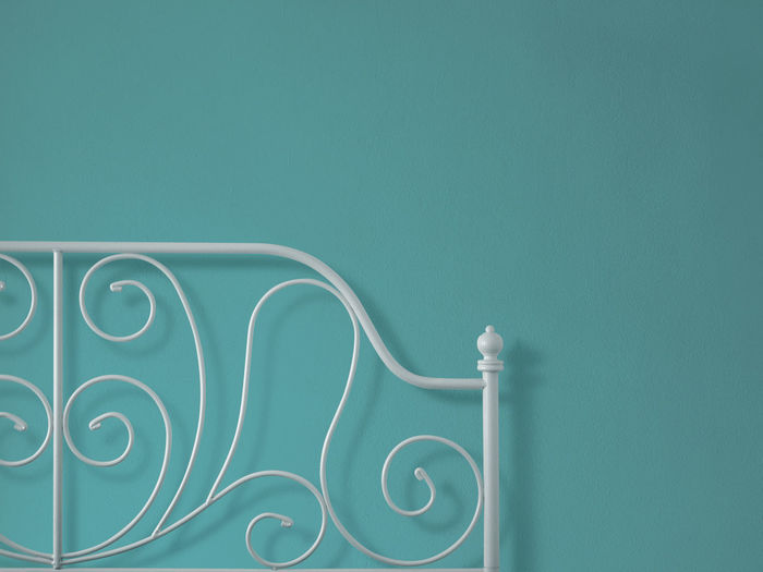 Close-Up Of Bed Against Blue Wall At Home