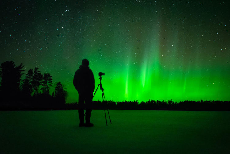 Rear view of silhouette man standing against sky at night with northern lights