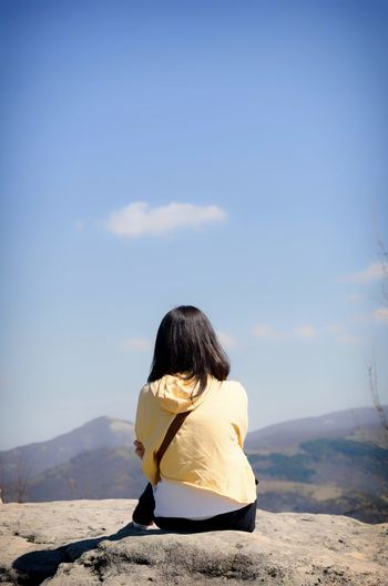 Rear view of girl sitting on mountain against blue sky
