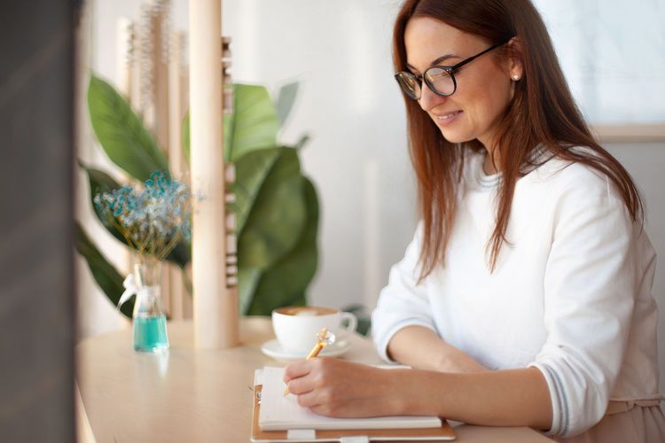 Smiling woman writing on diary while sitting at office